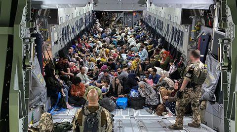 Evakuierte Menschen sitzen in Flieger auf dem Boden