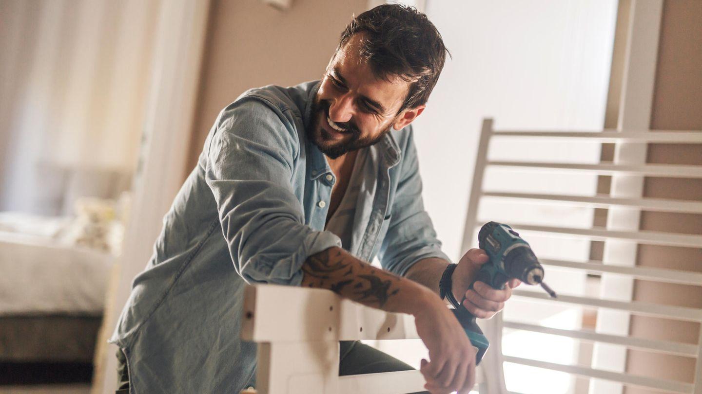 Ein Mann stützt sich mit Bohrschrauber in der Hand auf einer Holzpalette ab.