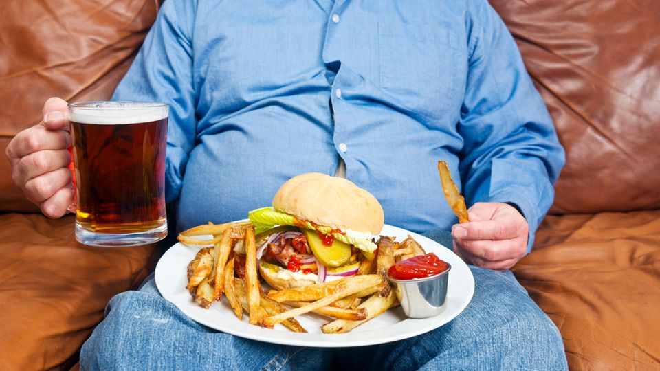 Ungesunde Ernährung: Ein dicker Mann sitzt mit Bier, Burger und Pommes auf dem Sofa