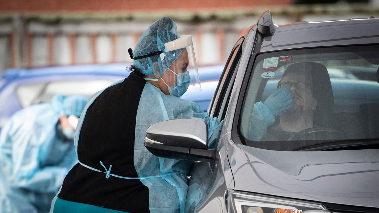 A motorist undergoes a COVID-19 test in a clinic