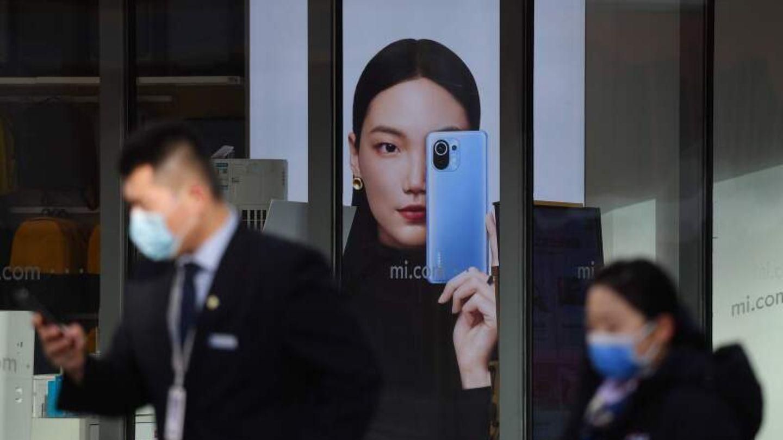 Menschen in Beijing gehen an einer Werbung für Smartphones vorbei