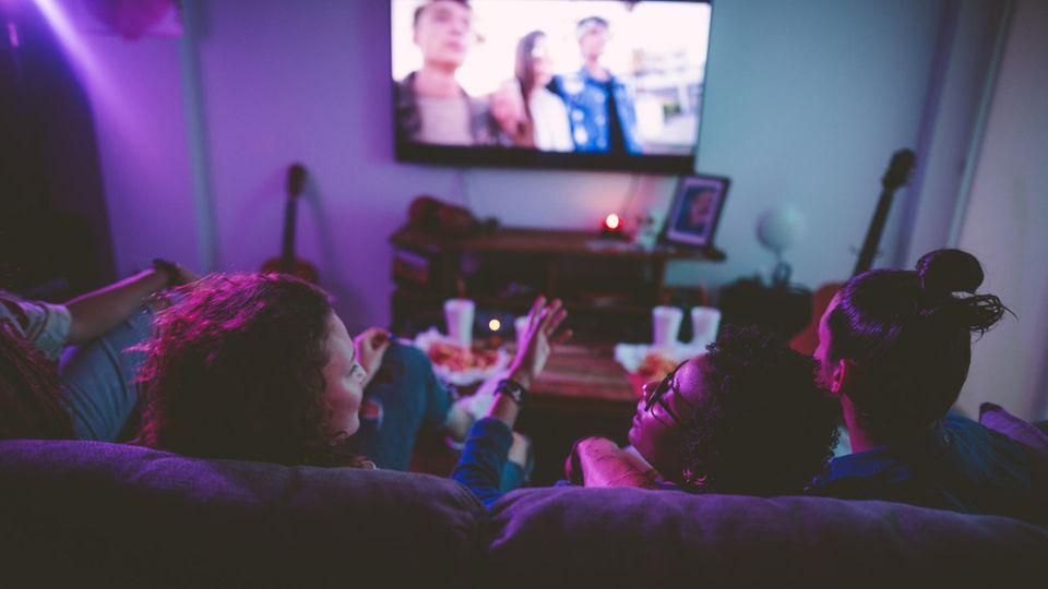 Drei Freunde sitzen vor einem Fernseher und unterhalten sich.