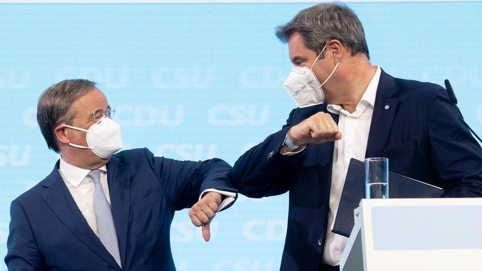 Armin Laschet und Markus Söder mit Schutzmasken beim Ellbogengruß