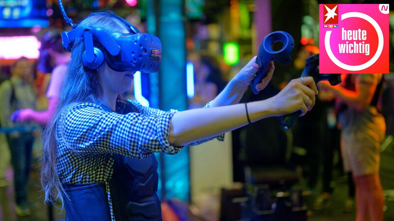 Eine Besucherin testet auf der Gamescom mit einer VR-Brille ein Computerspiel