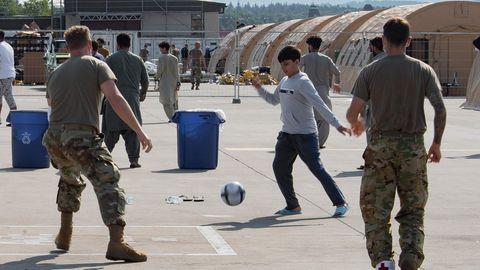 Ein Junge aus Afghanistan spielt mit US-Soldaten Fußball aufder Ramstein Air Base in Rheinland-Pfalz