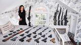 Bree Michael Warner, 43,posiert mit ihren Schusswaffen in ihrem Schlafzimmer im Putnam Valley, New York. Bree arbeitete als Schauspielerin und Moderatorin von Fernsehsendungen in Kalifornien, wo sie Mitglied der National Rifle Association und Ausbilderin für Schusswaffen wurde. Heute lebt sie in New York und bringt Frauen das Schießen bei, sowohl zur Selbstverteidigung als auch als Zeitvertreib.