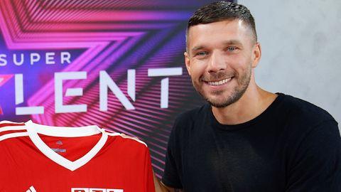 Lukas Podolski lacht beim Fototermin im Juli in die Kamera