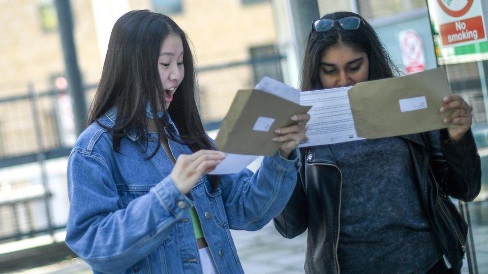 Zwei Studentinnen schauen in Briefumschläge, eine freut sich, eine nicht