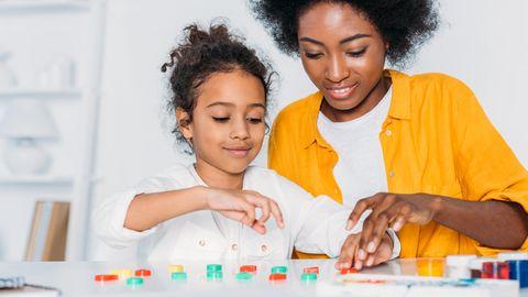 Mutter und Tochter sitzen mit farbigen Klötzchen am Tisch