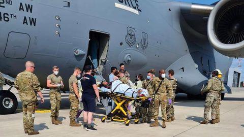 Flugzeug, Militär und die Mutter auf einer Trage auf dem Rollfeld