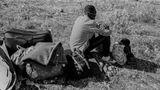 Ein Mann und ein kleines Mädchen mit ihrem Besitz etwas abseits von den Protesten im Flüchtlingscamp Moria.