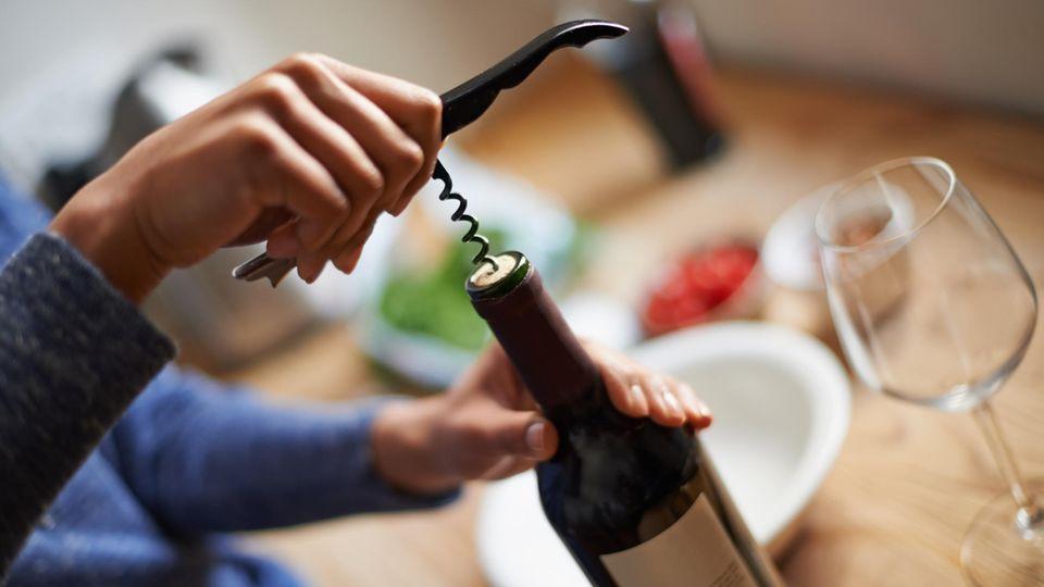 Weinöffner: Mann öffnet Weinflasche mit einem Kellnermesser