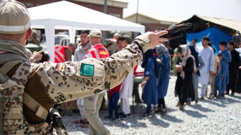 Soldaten und Helfer verteilen eine Spende an Menschen, die auf eine Ausreisemöglichkeit warten