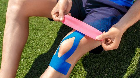 Kinesiotape: Mann behandelt sein Knie mit Kinesiotapes