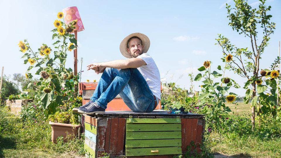Ein junger Mann sitzt im Garten, er sieht nachdenklich aus