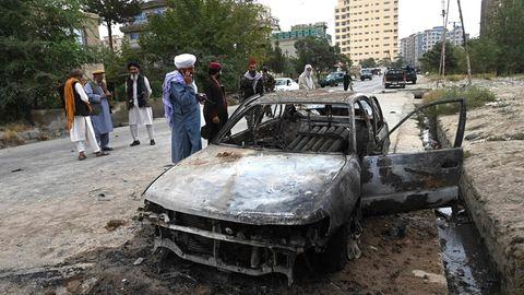 Taliban-Kämpfer stehen in Kabul neben dem ausgebranntem Wrack eines Autos