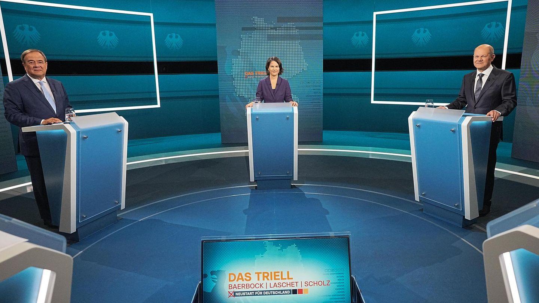 In einem blau beleuchteten TV-Studio stehen zwei Männer und eine Frau an einzelnen Pulten