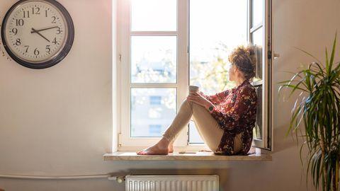 Eine Frau sitzt auf der Fensterbank und schaut nach draußen
