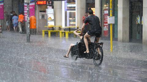Zwei junge Menschen fahren auf einem Lastenrad - einer auf dem Sattel, einer vorne im Gepäckfach - durch Regen in Berlin