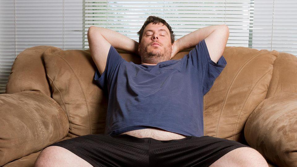 Ein Mann sitzt mit geschlossenen Augen auf dem Sofa