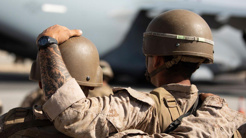 Von hinten sind zwei Soldaten in Tarnfleck und mit Helmen zu sehen. Einer legt dem anderen eine Hand auf den Helm