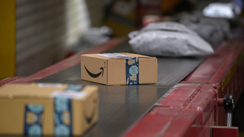 Amazon Pakete liegen im DHL-Paketzentrum auf einem Transportband.