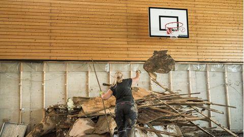 Unter dem Basketballkorb werfen die Eltern die vom Hochwasser zerstoert Einrichtung auf einen Haufen