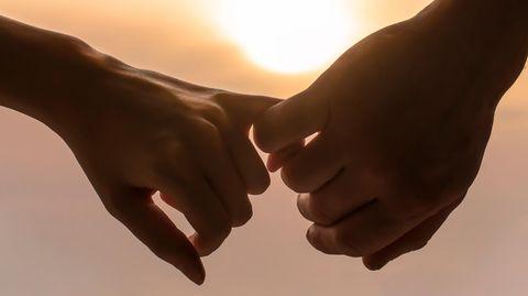 Zwei Hände halten sich an den Fingern im Sonnenuntergang