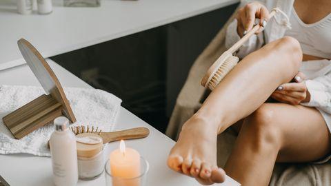 Frau streicht mit Trockenbürste über ihr Bein