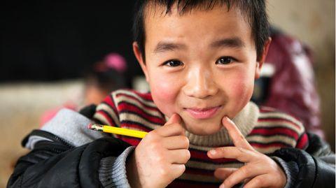 Junger chinesischer Schüler am Schultisch