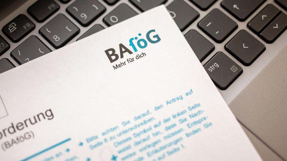 Ein Antrag auf Ausbildungsförderung (Bafög) liegt auf der Tastatur eines Laptop.