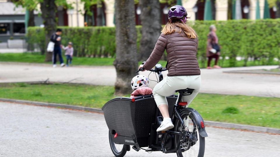 In großen Städten längst bewährt: Eine Mutter nutzt das Lastenfahrrad in München, um ihr Kind zu transportieren