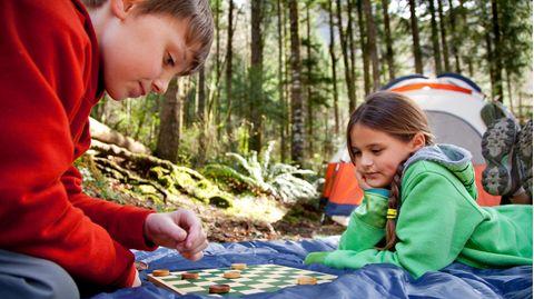 Zwei Kinder spielen ein Brettspiel im Freien