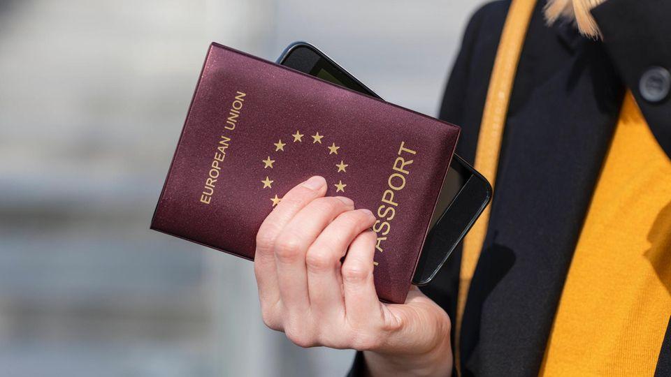 Eine Frau hält einen Ausweis und ein Smartphone in der Hand.