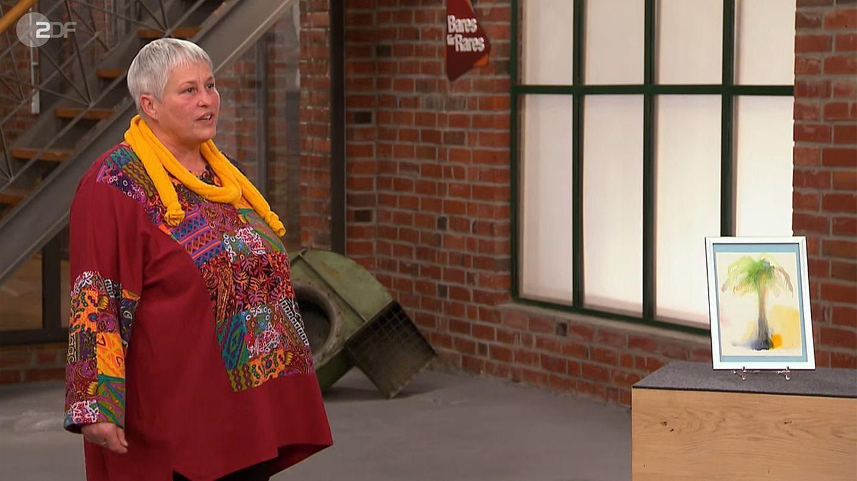 Monika Tensing steht im Studio von Bares für Rares neben dem Aquarell von Janosch