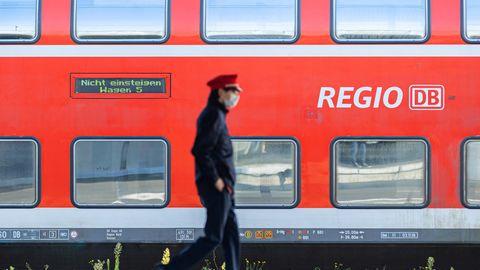 Ein Mitarbeiter der Deutschen Bahn (DB) läuft auf einem Bahnsteig und ein Zug der DB Regio steht auf einem Gleis dahinter