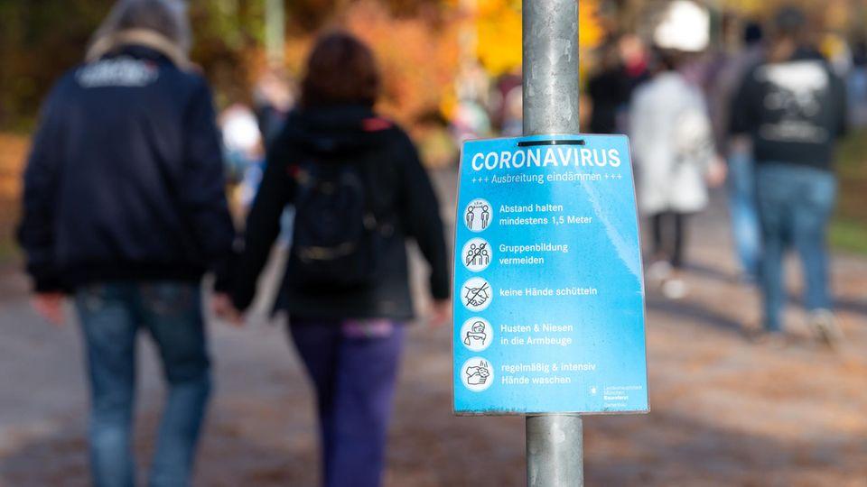 Ein Plakat mit Informationen über das Coronavirus ist an einem Weg im Westpark zu sehen