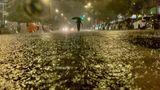 Im Dunkeln sind die Konturen eines Menschen zu sehen, der eine überflutete Straße hinunterläuft