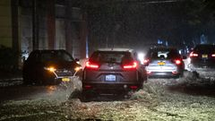 Im Dunkeln leuchten die Rücklichter mehrerer Autos, die auf einer überschwemmten Straße auf Staten Island fahren