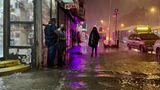 Zwei Männer unterhalten sich vor einem beleuchteten Eck-Laden, während auf überflutetem Fußweg ein Mensch in Regenponcho geht