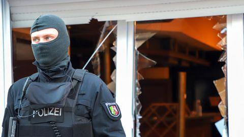 Ein Polizist steht mit Sturmhaube vor den zerborstenen Fenstern eines Vereinsheims der Hells Angels in Mönchengladbach