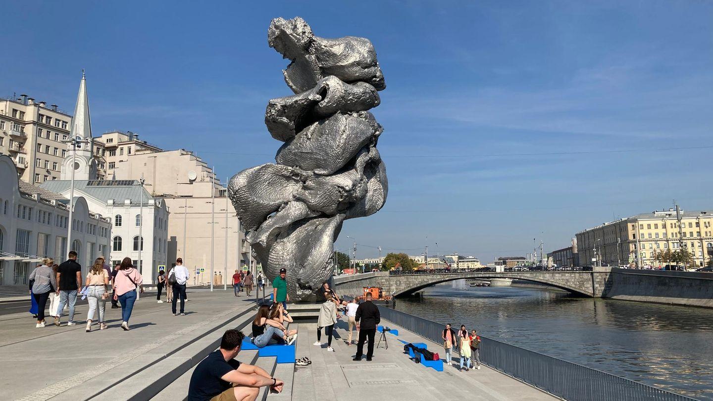 Menschen sitzen neben der Skulptur des Künstlers Urs Fischer in Moskau. Über das Aussehen des Kunstwerks wird gestritten.