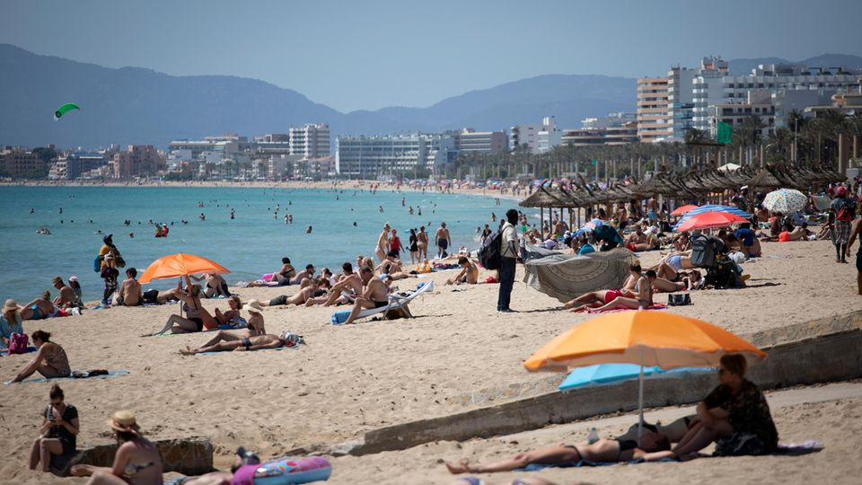 Menschen liegen in der Sonne an einem Strand