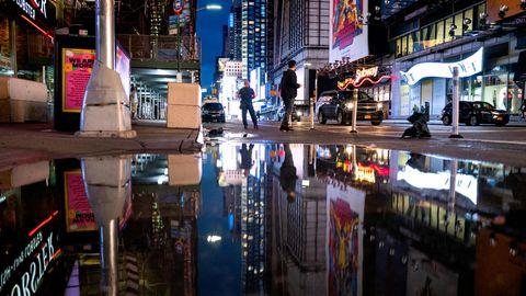 Die Neon-Reklamen des Times Square spiegeln sich in einer riesigen Pfütze