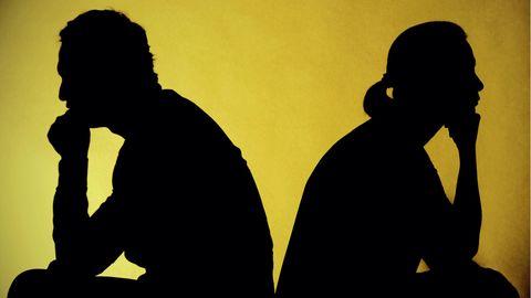 Mann und Frau im Profil sitzen voneinander abgewandt