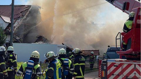Einsatzkräfte der Feuerwehr, auf dem Foto ist auch Rauch zu sehen