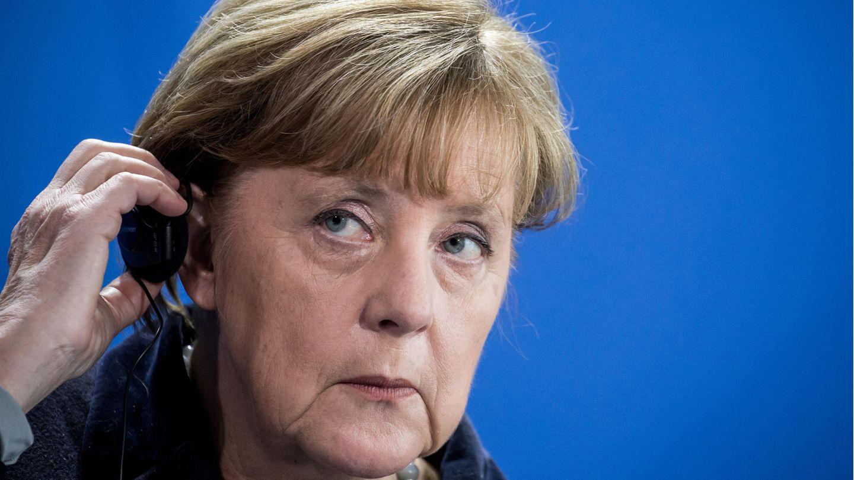 Bundeskanzlerin Angela Merkel hält einen Kopfhörer an ihr Ohr