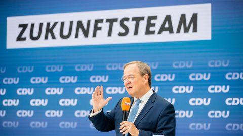 """Ein Mann in Anzug und Krawatte spricht unter dem Schriftzug """"Zukunftsteam"""" in ein orangenes Mikrofon"""
