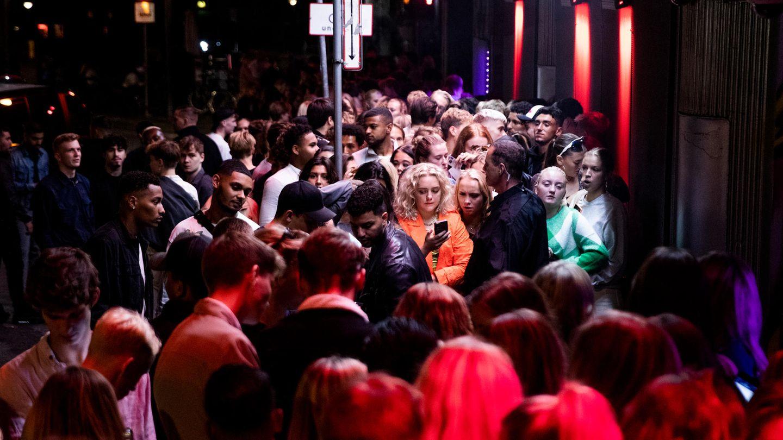 Menschen drängen sich in der Nacht vor einem Nachtclub