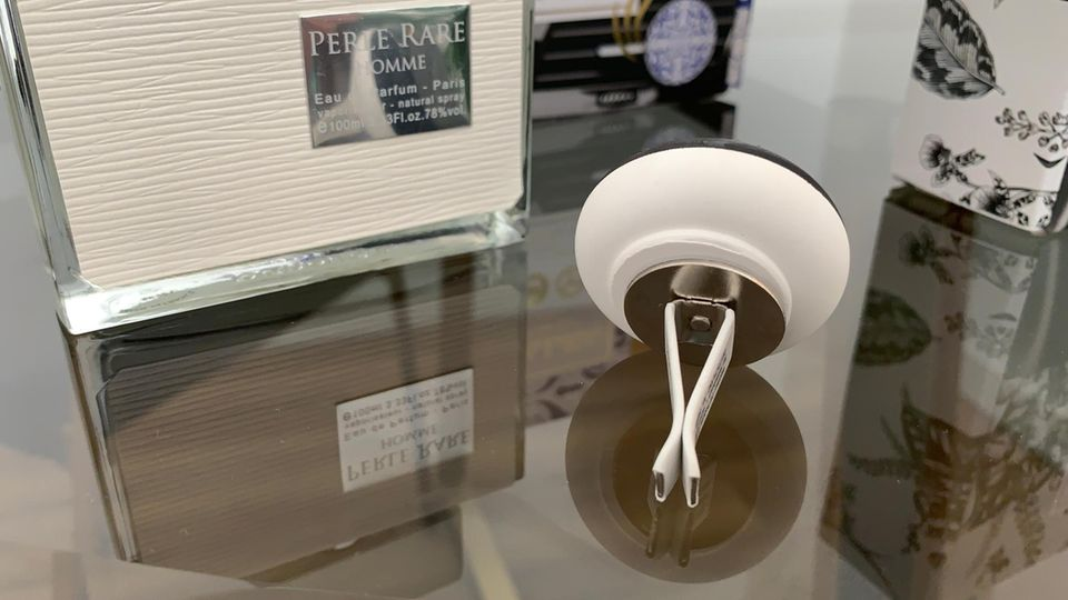 Der Clip für die Lüftung ist mit dem Stein verbunden – im Hintergrund ist das Parfüm zu sehen.